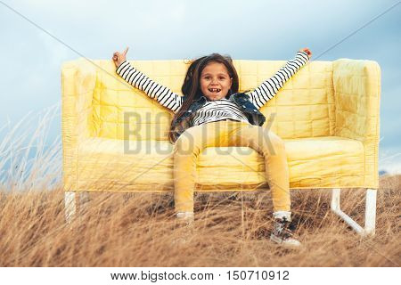 7 years old child sitting on a sofa in the autumn field outdoor.