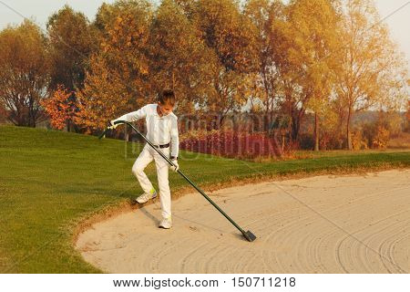 Boy golf player rake the bunker area from footprints at autumn sunset