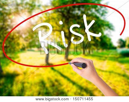 Woman Hand Writing Risk With A Marker Over Transparent Board