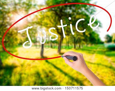 Woman Hand Writing Justice With A Marker Over Transparent Board
