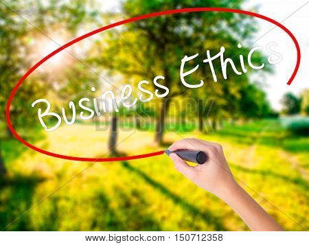 Woman Hand Writing Business Ethics With A Marker Over Transparent Board