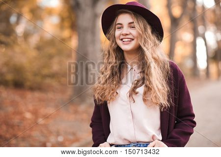 Smiling teenage girl 14-16 year old walking in autumn part. Wearing hat and jacket outdoors. Happiness.
