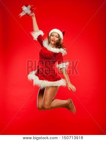 christmas, x-mas, winter, happiness concept - smiling woman in santa helper hat with gift box, happiness jump for joy over red background