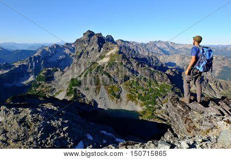 Climber Looking Towards Lake and Alpine Skyline.  Chickamin Peak, The Alpine Lakes Wilderness, Washington