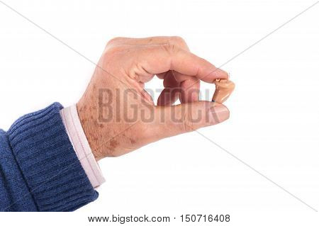 Close up of a senior man's hand showing a CIC (Completely In Canal) hearing aid between his fingers. Studio shot isolated on white.
