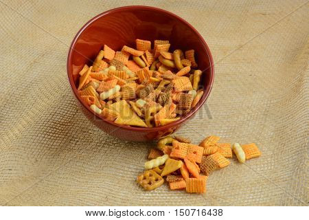 Red Bowl full of cheese flavored party snacks on burlap