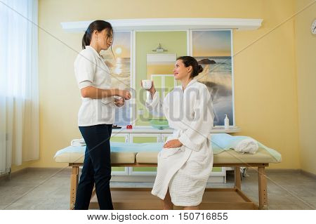 Pretty young woman wearing a robe and masseuse talking after massage in a spa drinking some tea.