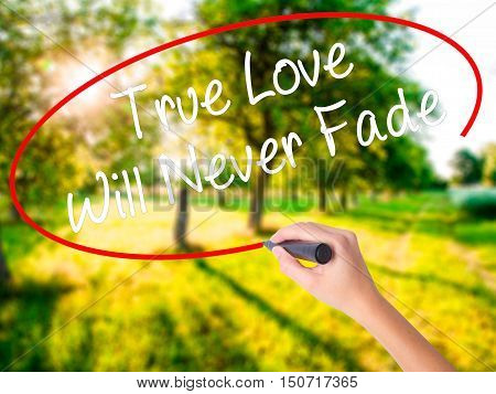 Woman Hand Writing True Love Will Never Fade With A Marker Over Transparent Board