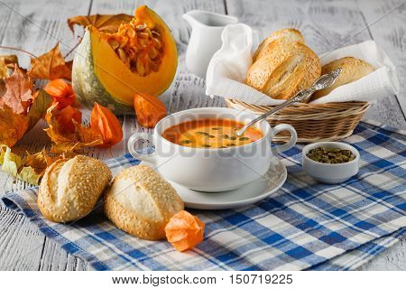 Creamy Butternut Squash Soup Topped With Pumpkin Seeds And Cream On Rustic Wood Background With Autu