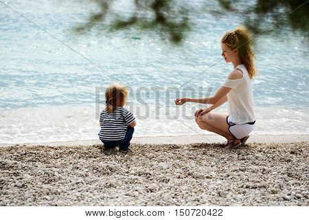 Mother young woman and son baby boy sit on pebble beach near blue sea windy weather on natural background