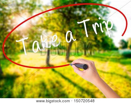 Woman Hand Writing Take A Trip With A Marker Over Transparent Board