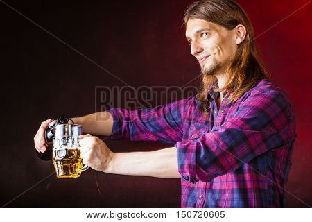 Alcohol liquor drinking relax party concept. Tapster fills stein from bottle. Young male bartender empties beer into glass.
