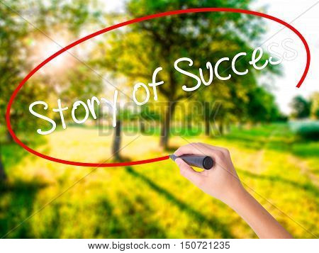 Woman Hand Writing Story Of Success With A Marker Over Transparent Board