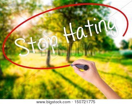 Woman Hand Writing Stop Hating  With A Marker Over Transparent Board