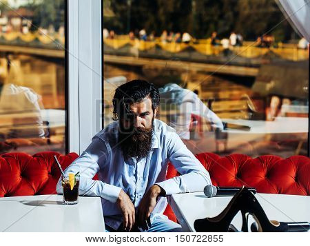 Bearded Man Between Two Tables