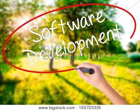 Woman Hand Writing Software Development With A Marker Over Transparent Board