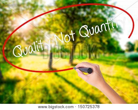 Woman Hand Writing Quality Not Quantity With A Marker Over Transparent Board