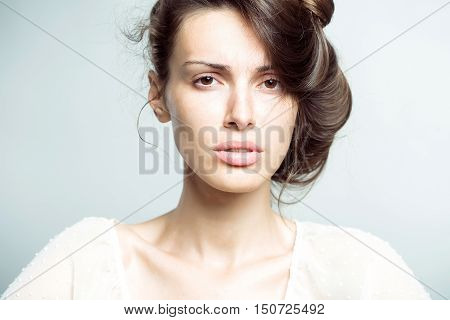 Pretty sensitive brunette in white shirt with collected hair on gray studio background