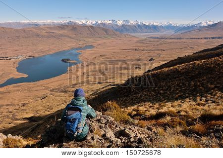 A Woman Hiker Looks Over Lake Clearwater Towards The Southern Alps.  Hakatere Conservation Park, Canterbury, Lake Clearwater, New Zealand