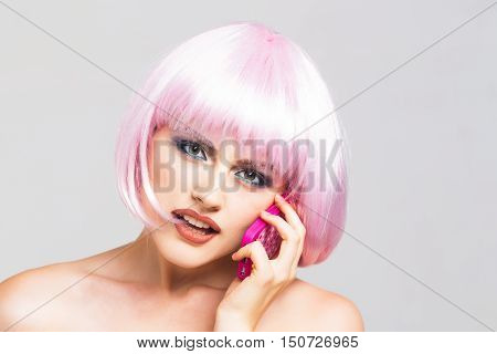 sexy glamour woman with fashionable makeup on pretty face and short hairstyle or pink wig holding plastic toy mobile phone in studio on light background