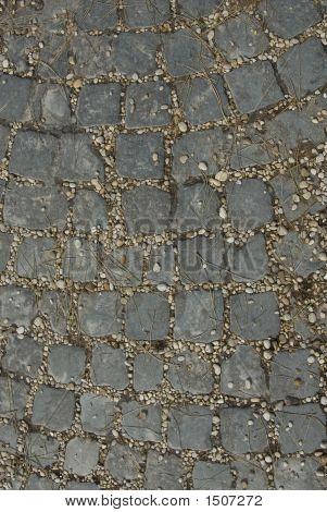 Steine zwischen Platten