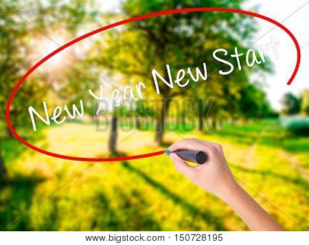 Woman Hand Writing New Year New Start With A Marker Over Transparent Board