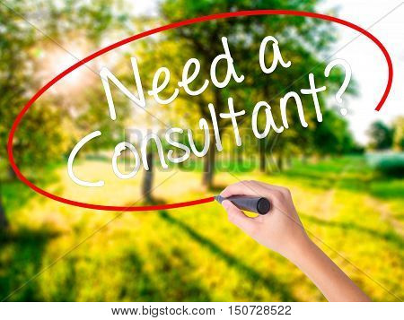 Woman Hand Writing Need A Consultant? With A Marker Over Transparent Board