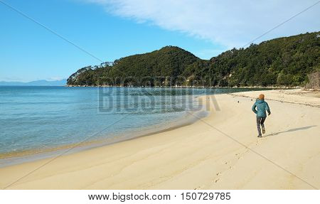 A Woman Running on Sandy Tropical Beach. Bark Bay Abel Tasman National Park New Zealand