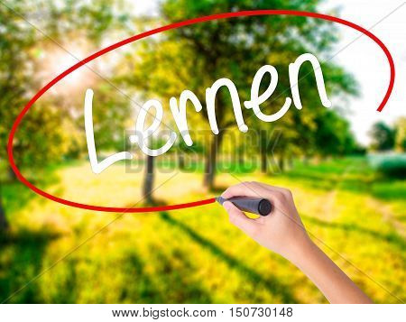 Woman Hand Writing Lernen (learn In German) With A Marker Over Transparent Board .