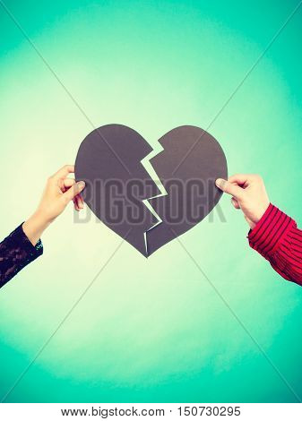 Reconcillation feelings romance concept. Two people fixing love. Hands holding halves of broken heart together.
