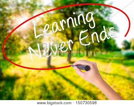 Woman Hand Writing Learning Never Ends With A Marker Over Transparent Board