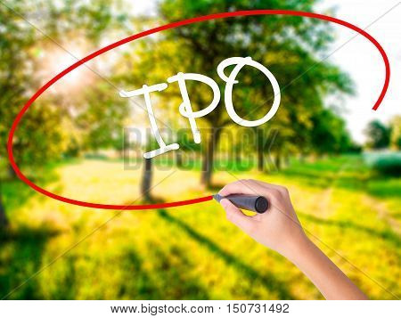 Woman Hand Writing Ipo (initial Public Offering)   With A Marker Over Transparent Board