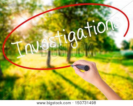 Woman Hand Writing Investigations With A Marker Over Transparent Board .