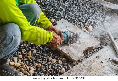 The worker cutting brick in construction site.