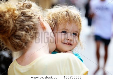 Mother young woman holds happy son baby boy with blonde hair in blue shirt sunny day outdoor in street on blurred background