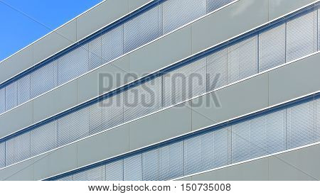 Wall of an office building with windows with closed shutters, blue sky.