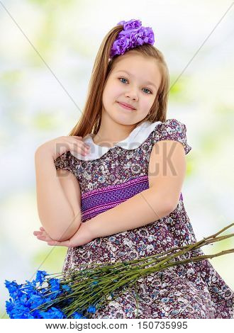 Happy little girl with a big purple bow on her head , and fancy dress. In the lap of the girls lay a bouquet of blue flowers.Summer green and white background.