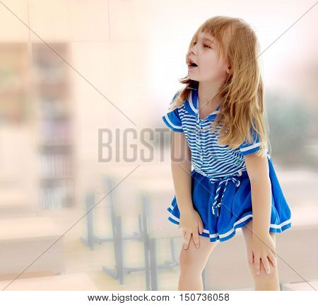 Cute little unkempt girl in a short blue dress. Girl looking to the side with his hands on his knees.The concept of raising a child in the family. In the class where there are school desks.