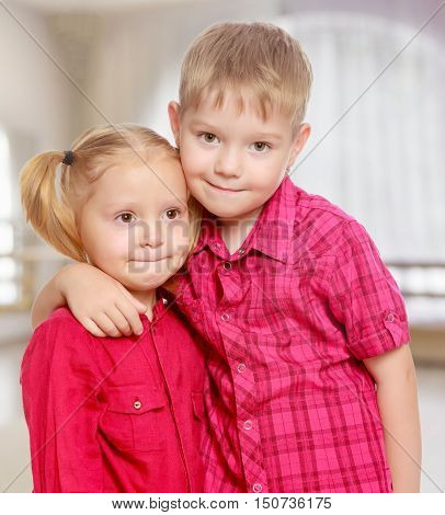 Little brother and sister cute hug.The concept of pre-school education of the child among their peers . in gaming room with a large arched window.