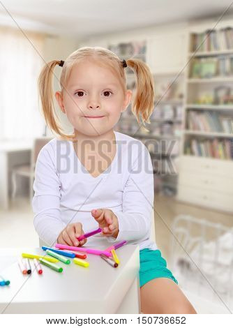 The concept of family happiness, and preschool education of the child , against a child's room with bookshelves.Pretty little blonde girl drawing with markers at the table.