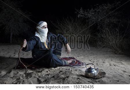 Man in traditional Tuareg outfit in a desert preparing tea