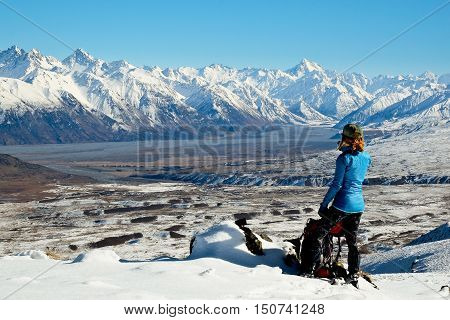 A Woman Hiker Pauses Takea a Break to Enjoy Mountain Views.  Hakatere Conservation Park, Southern Alps, New Zealand