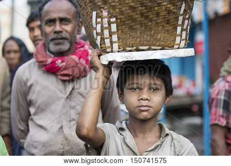 Chittagong Bangladesh February 25th 2016: Young boy carrying a basket on his head at a market