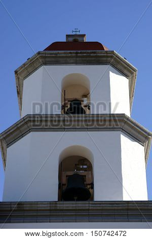 A bell tower of the Mission Basilica San Juan Capistrano with bells over each other.
