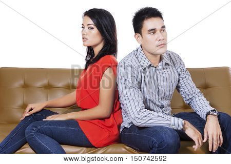 Angry couple sitting sitting opposite each other on the brown sofa isolated on the white background