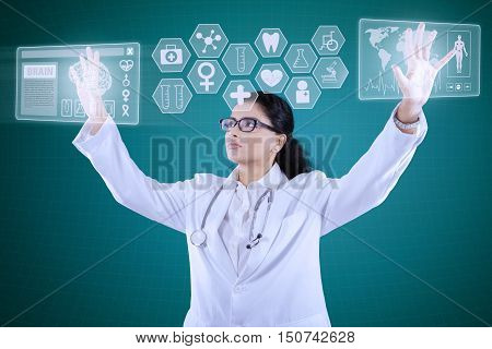 Portrait of Indian female doctor wearing lab coat and stethoscope while her hands pressing on virtual screen