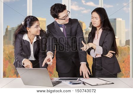 Portrait of business team having problem working in the workplace and pointing at laptop with autumn background on the background