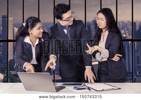 Image of boss and secretary pointing at laptop to show the mistake of their employees with tablet and paperwork on the table