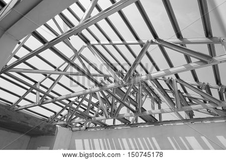 Black and white photoStructure of steel roof frame for building construction.The advantage of this structure is lightweight but strong.