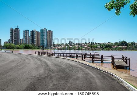Beautiful sunny day in a park with a walking trail, an observation deck over lake water, buildings and background trees. blue sky, a beautiful day to relax and do exercises in the park.